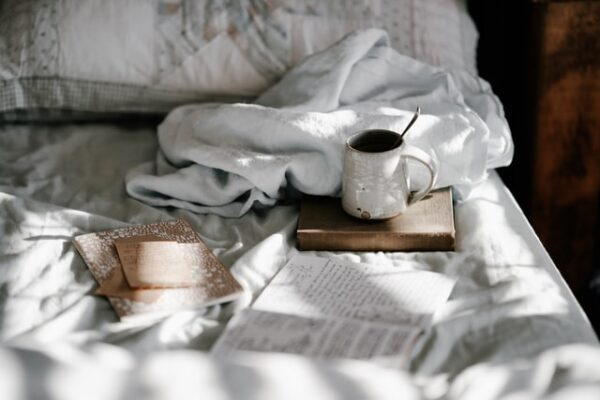 Unmade bed with some books and a towel. A mug of tea is standing on one of the books.