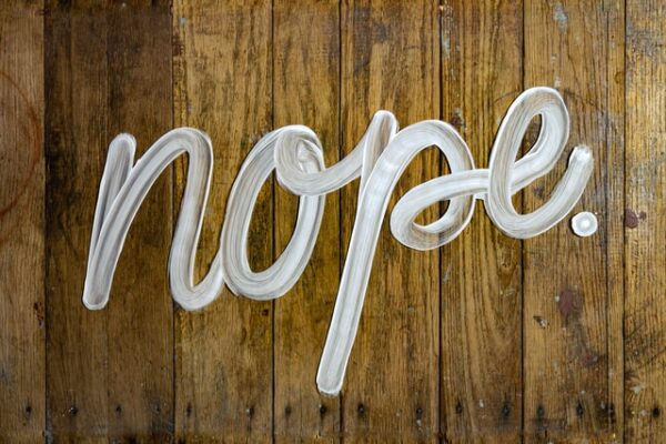 """Text reading """"nope"""", handwritten with white marker on a wooden background."""