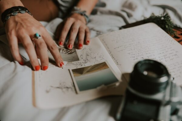 Two hands of a woman are adding pictures to a notebook. The notebook is a journal which can be used as a self-care tool.